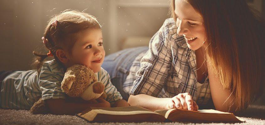 Mutter liest kleinem Mädchen ein Buch vor