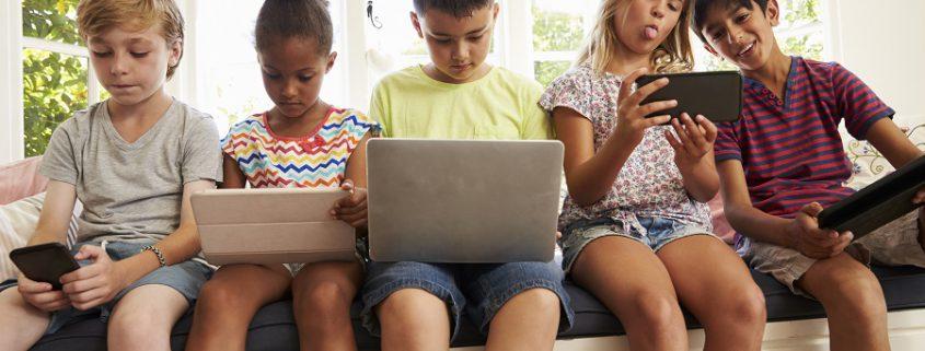Kinder beschäftigen sich mit Laptop und Handy in der Hand