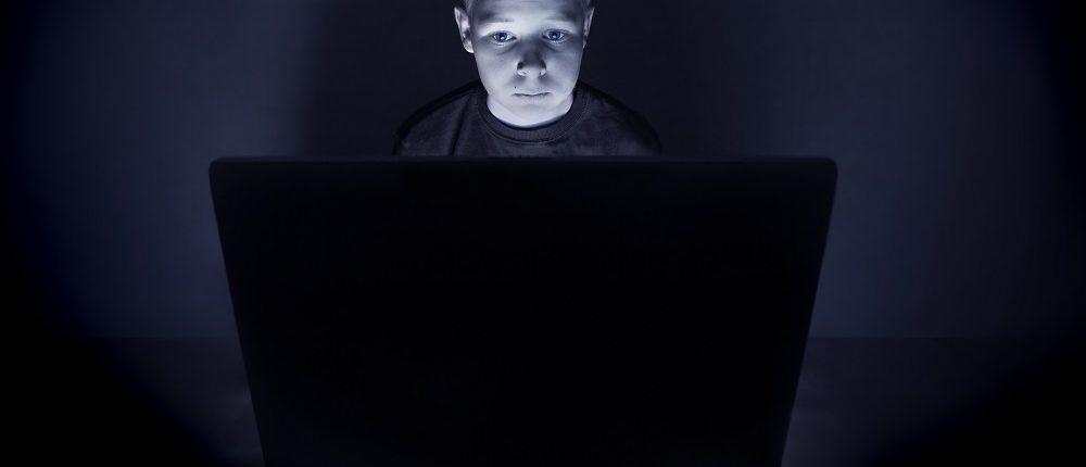 Junge sitzt im dunklen Zimmer am Laptop