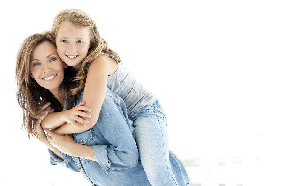Mutter trägt Tochter auf dem Rücken