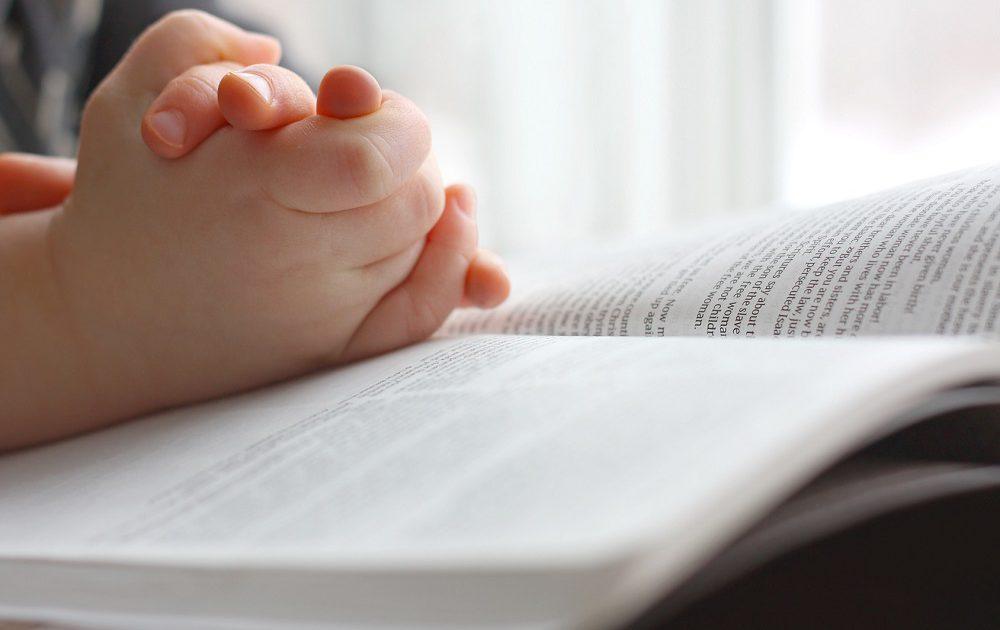 Kinderhände sind über einer Bibel zum Gebet gefalten