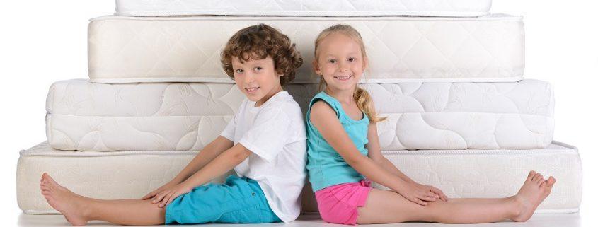 Junge und Mädchen sitzen vor einem Berg aus Matratzen