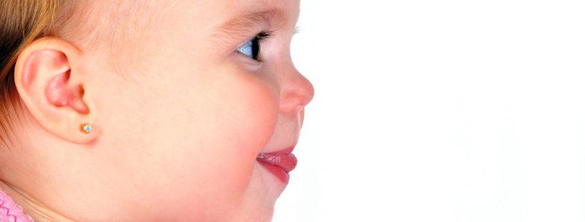 Kleines Baby Mädchen mit Ohrringen.