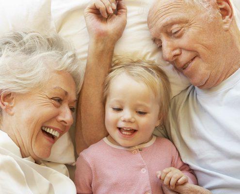 Großeltern kuscheln mit Kind