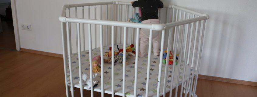 Baby steht in dem Geuther Laufgitter Matrix 6-eckig weiss
