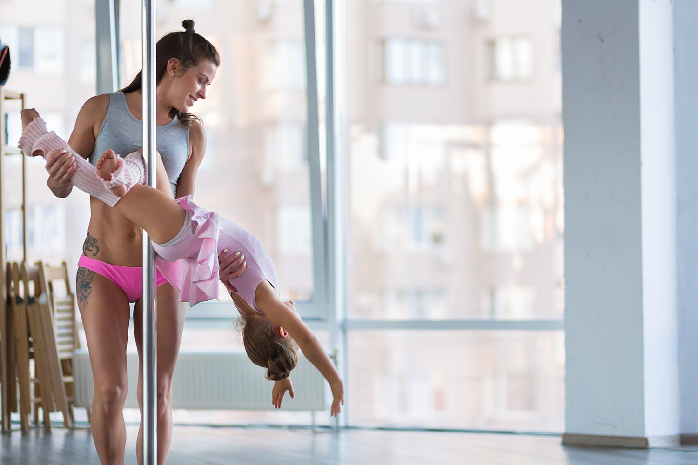 Mädchen zeigt ihr Können beim Pole Dance.