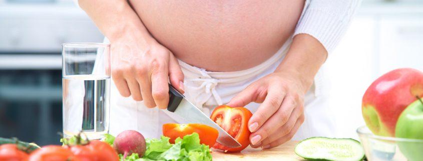 Schwangere schneidet buntes, frisches Gemüse.
