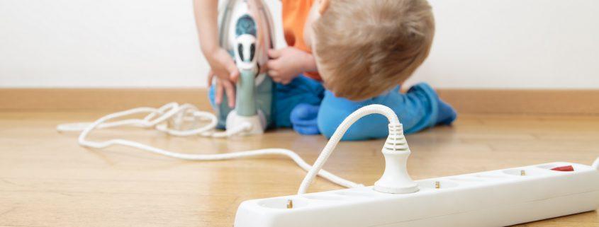 Verbrennungsgefahr bei Kind, das mit Bügeleisen spielt.