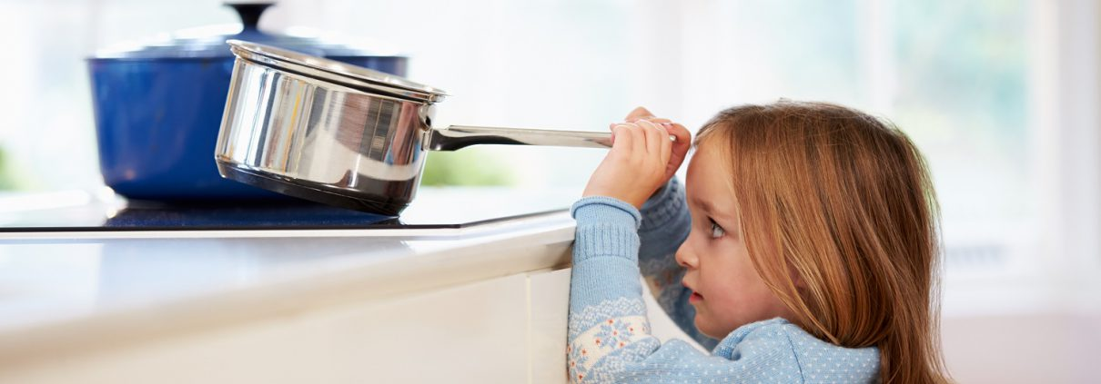Verbrennungsgefahr bei Kind, das einen Kochtopf vom Herd nehmen will.