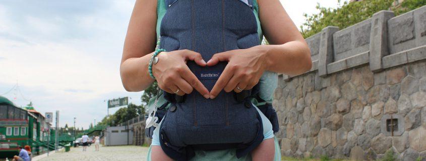 Frau formt Herz mit Fingern auf Babybjörn Babytrage One Cotton Mix Classic Jeans Mitternachtsblau