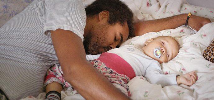 Vater und Baby schlafen im Bett