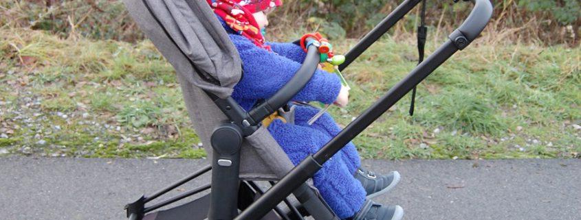 Blaugekleidetes Kleinkind sitzt im Sportsitz des Cybex Platinum Kinderwagen Priam Sets