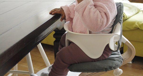 Mädchen isst im nomi Hochstuhl Komplettset in weiß vor Couchlandschaft