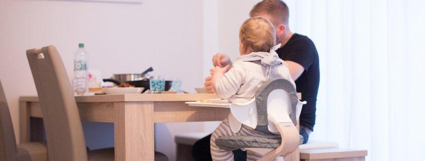 Mann isst am Esstisch zusammen mit Mädchen im nomi Hochstuhl Komplettset in weiß