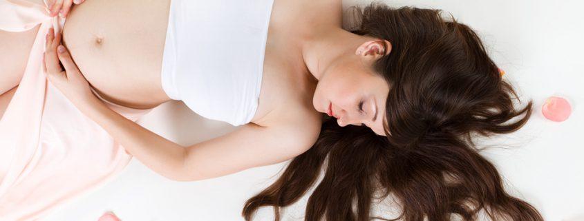 Schwangere Frau liegt mit offenen Haaren