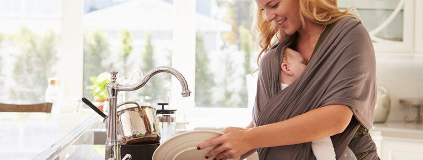 Frau trägt Baby beim Geschirrspülen in Babytrage
