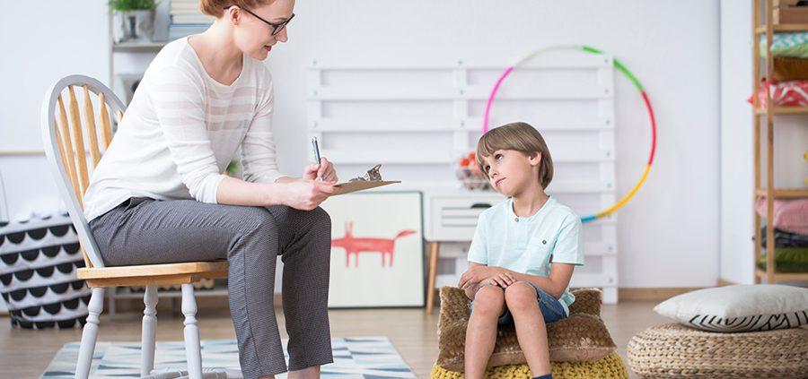 Kind sitzt auf einem Ball und spricht mit euer Frau.