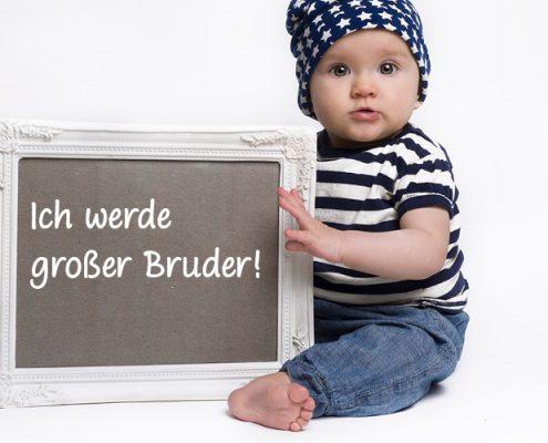 """Schwangerschaft verkünden mit Geschwisterchen. Junge mit """"Ich werde großer Bruder""""-Plakat"""