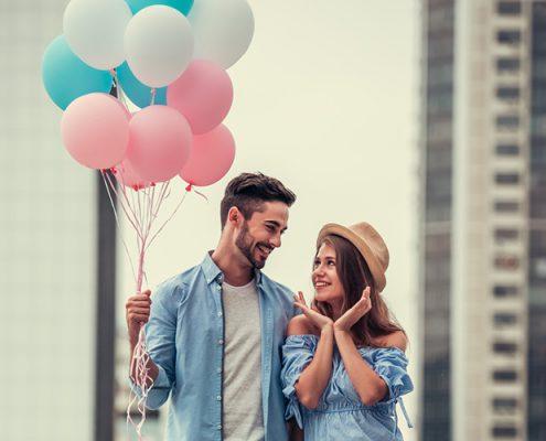 Schwangerschaft verkünden mit Luftballons. Pärchen hält blaue, rosane und weiße Luftballons in der Hand