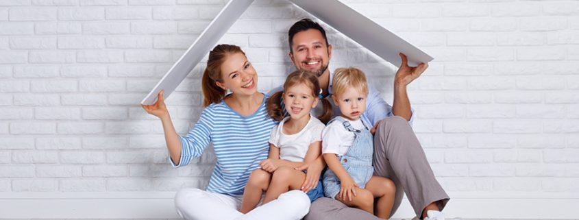 Familie hält symbolisch Dach über sich