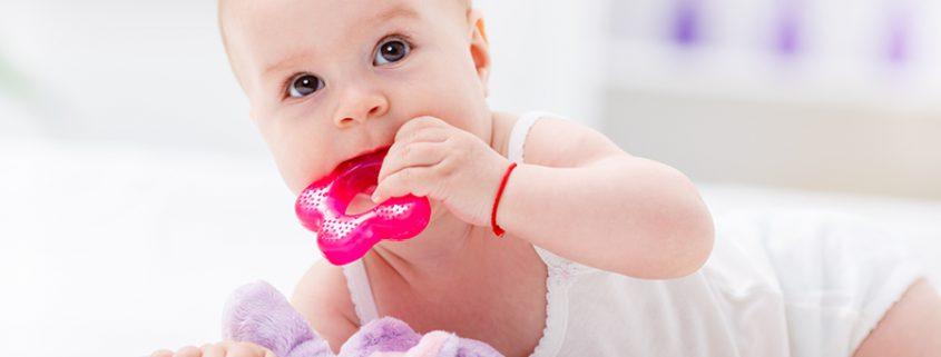 Baby hat Spielzeug im Mund