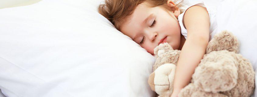 Mädchen kuschelt mit Stofftier und schläft.