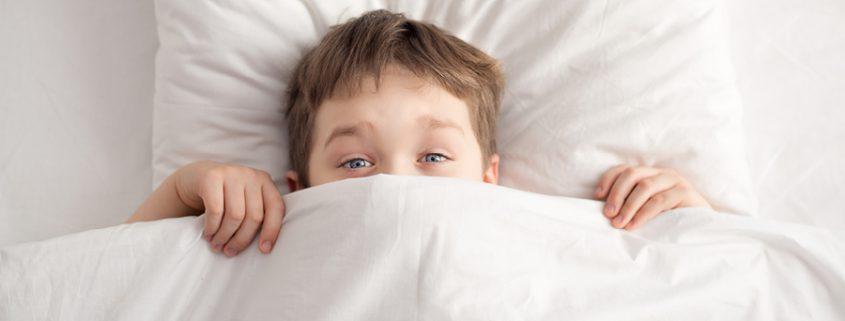 Junge zieht sich die Bettdecke über das Gesicht