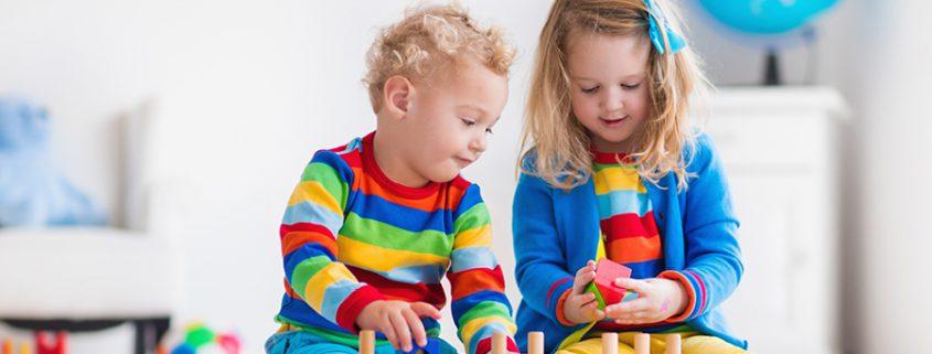 Mädchen und Jungen spielen mit Bauklötzen
