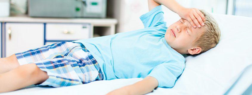 Junge liegt auf Liege beim Arzt und hält sich den schmerzenden Kopf
