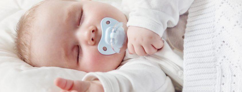 Baby schläft mit Schnuller im Mund