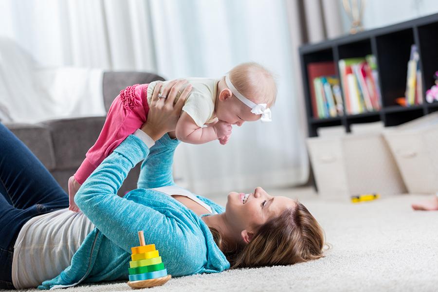 Frau hebt Kleinkind in die Luft und liegt dabei auf dem Boden