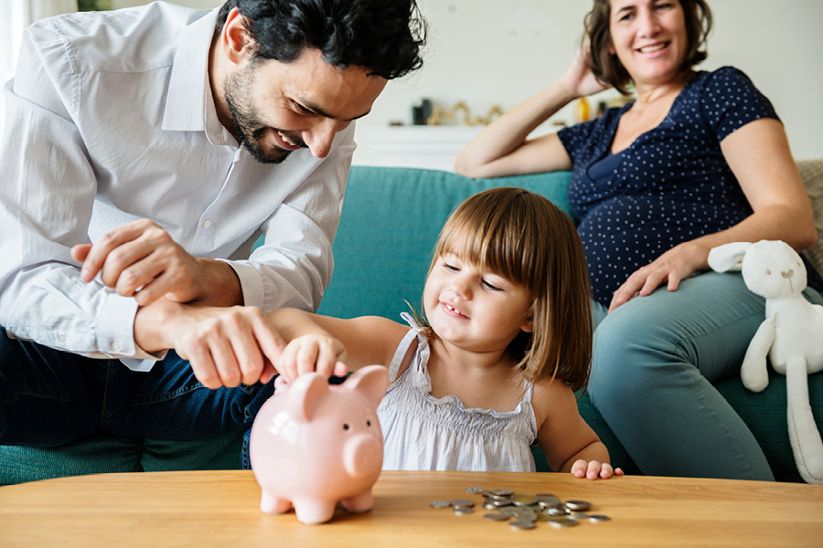Familie mit Kind wirft Geld ins Sparschwein