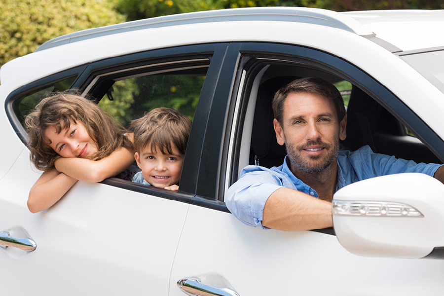 Vater und Kinder schauen aus dem Auto