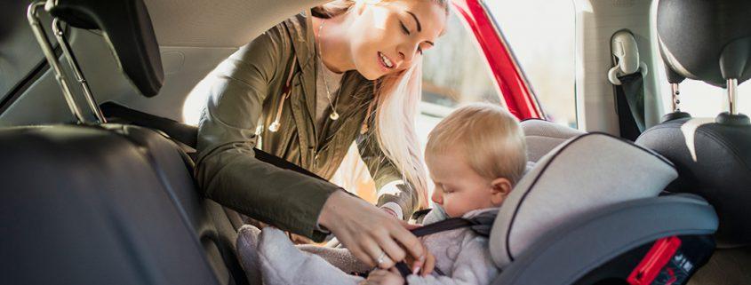 Baby ist im Reboarder und wird von Frau angeschnallt