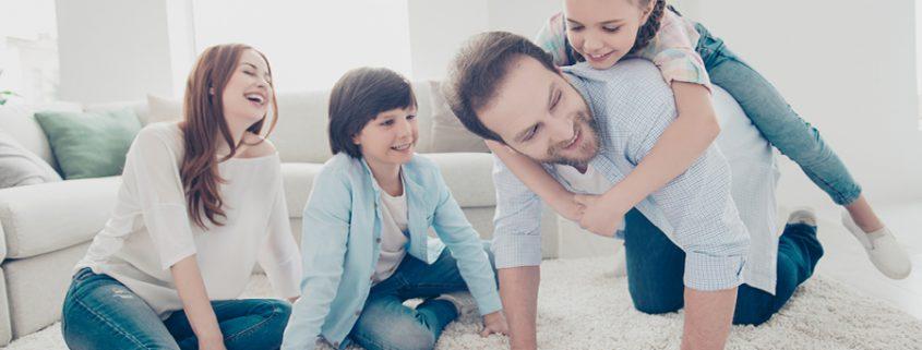 Eltern spielen mit ihren zwei Kindern auf dem Boden