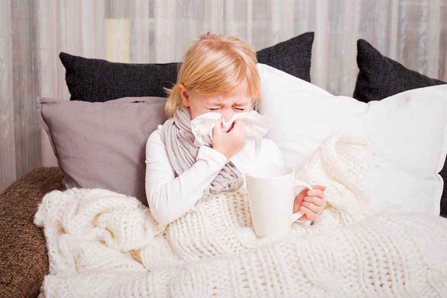 Ein Mädchen schnäuzt sich die Nase und sitzt zugedeckt auf dem Sofa