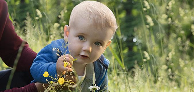 Baby sitzt im Gras