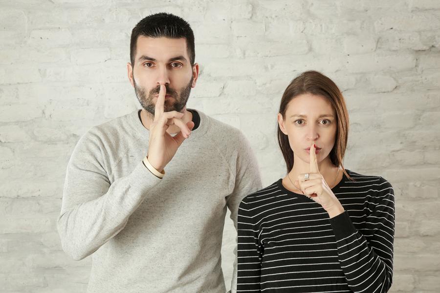 Frau und Mann halten Finger vor ihrem Mund