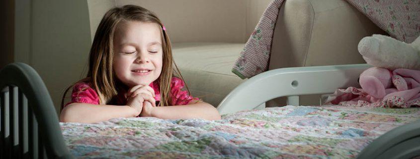 Kleines Mädchen sitzt vor ihrem Bett und betet