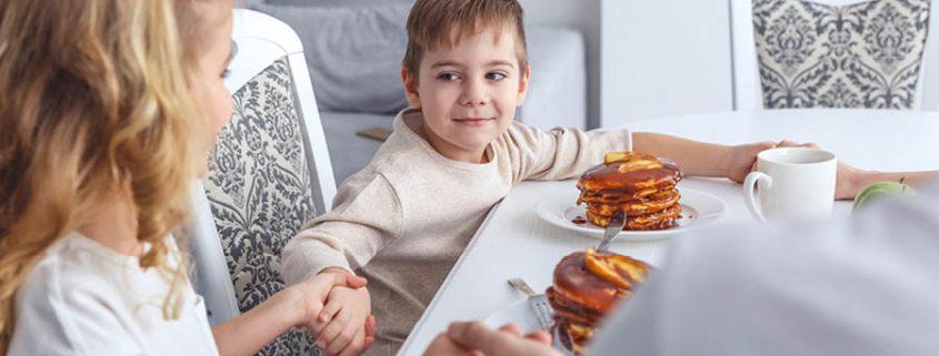 Kinder sitzen an einem Tisch und halten die Hände