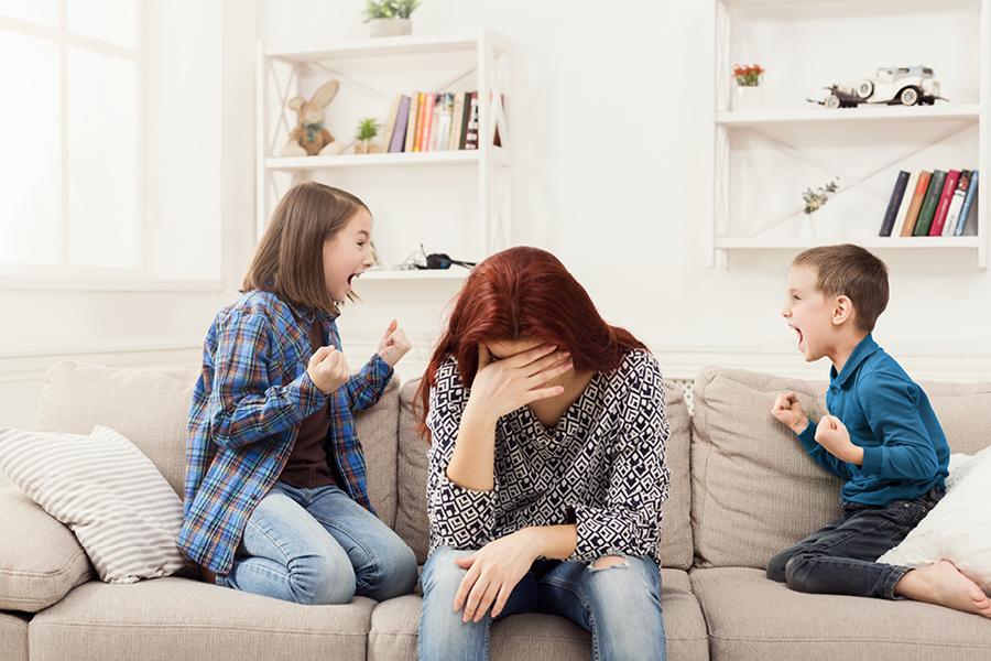 Frau hält sich Hände vor das Gesicht während Kinder auf der Couch toben
