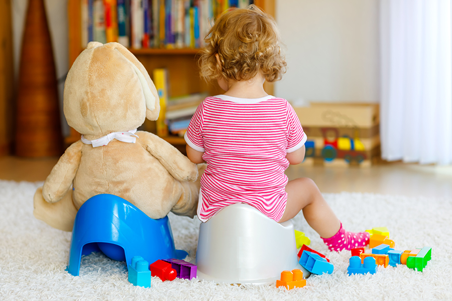 Kind sitzt neben seinem Kuscheltier auf dem Töpfchen