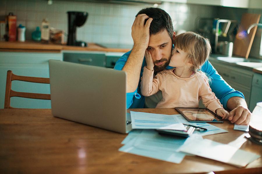 Vater schaut erschöpft auf den Monitor während Kind ihm einen Kuss gibt.