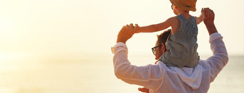 Baby, das auf den Schultern seines Papas sitzt mit Sonnenuntergang