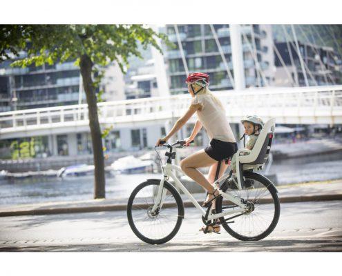 Mutter fährt mit Kinderfahrradsitz Fahrrad