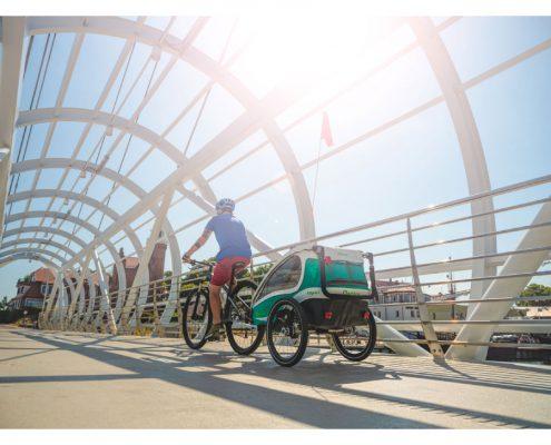 Mann fährt mit Kinderfahrradanhänger hinten dran Fahrrad