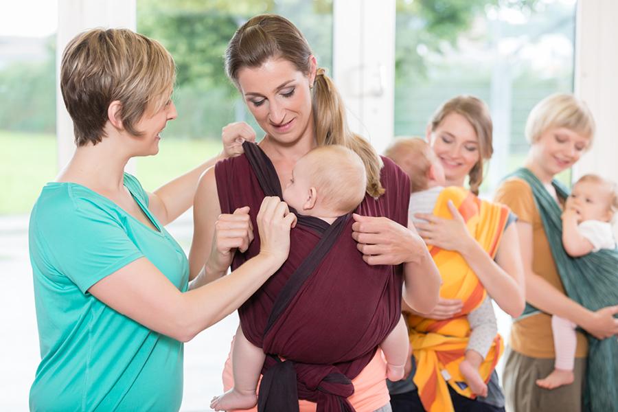 Frau hilft Mutter bei Tragehilfe für Baby