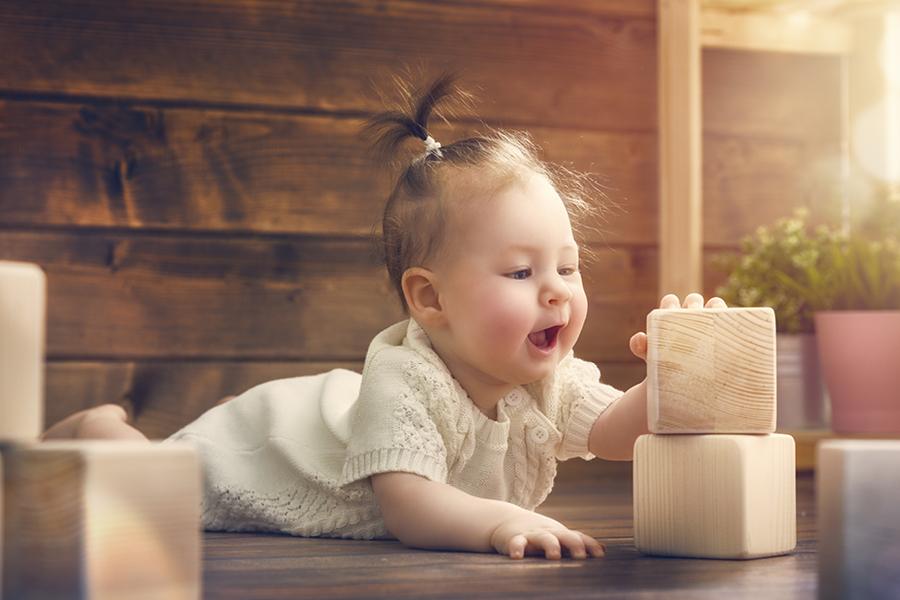 Kleinkind spielt mit Holzbausteinen