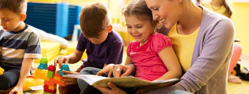 Erzieherin ließt Kind aus einem Buch vor