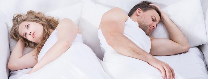 Mann und Frau liegen Rücken an Rücken im Bett.